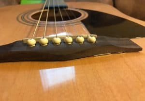 An acoustic guitar bridge coming unglued from the body