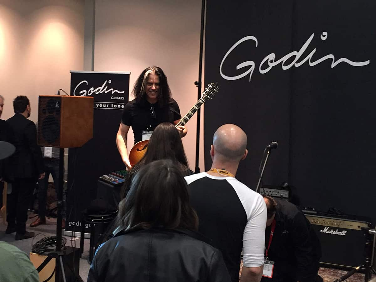 Alex Skolnick posing for a photo on stage in the Godin Guitars room at NAMM 2018