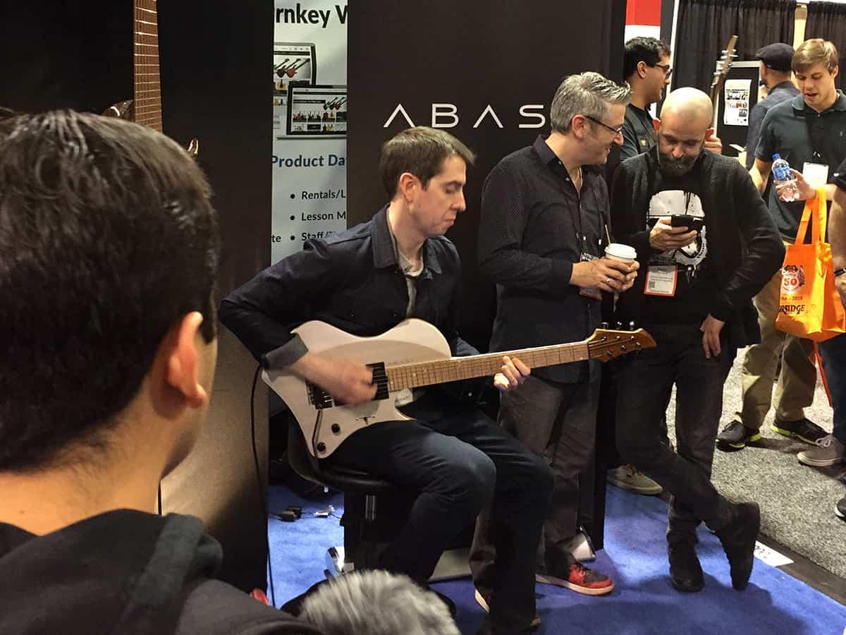 "Thomas ""McRocklin"" McLaughlin trying one of the Abasi 6-string guitars at NAMM 2018"