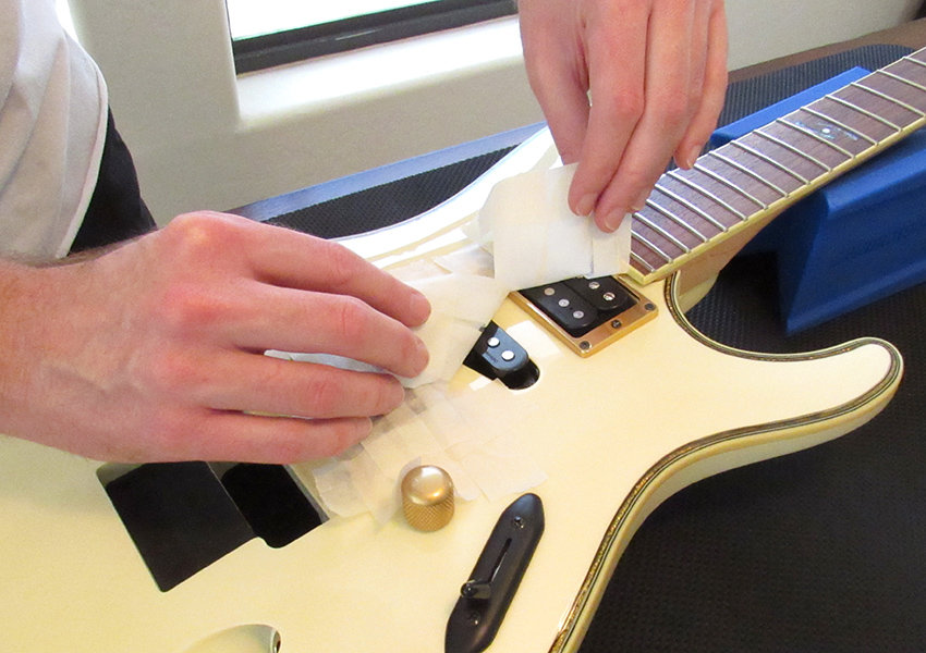 Carefully remove all tape from the guitar
