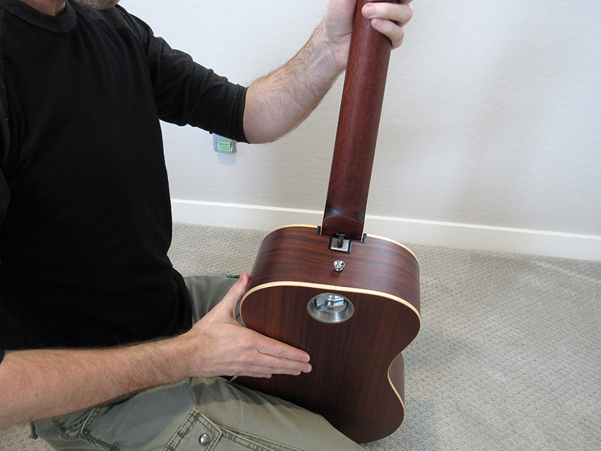Hold the guitar body gently between your knees when attaching the neck