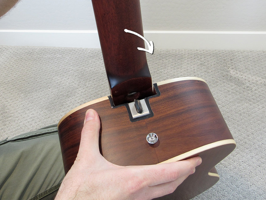 Seat the front-lip of the neck into the pocket first, then tilt the headstock backward into the neck pocket