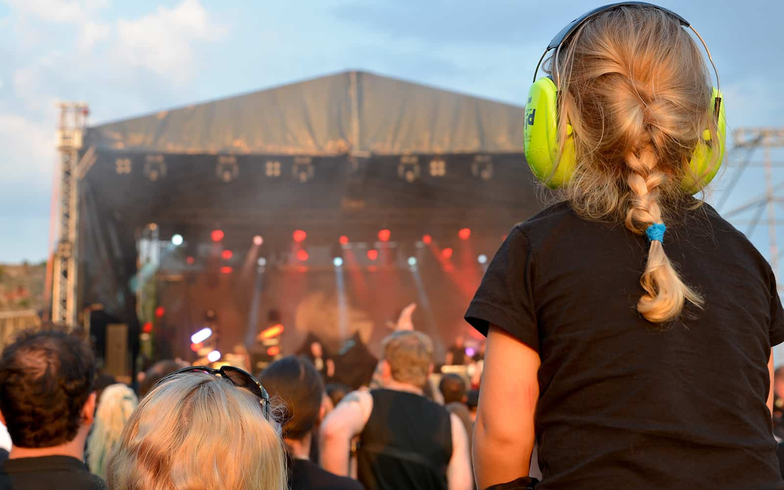 Child at live concert, wearing ear protection