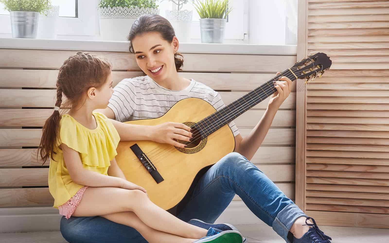 A mother plays guitar for her daughter