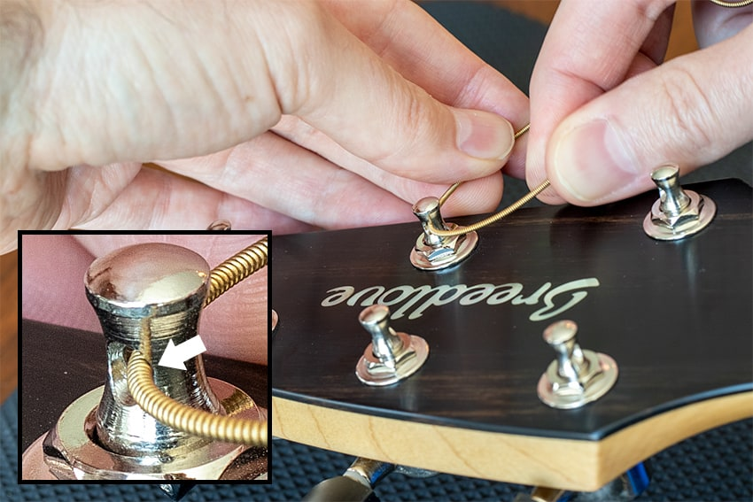 Bending the guitar string so it contacts the sharp edge of the tuning post hole