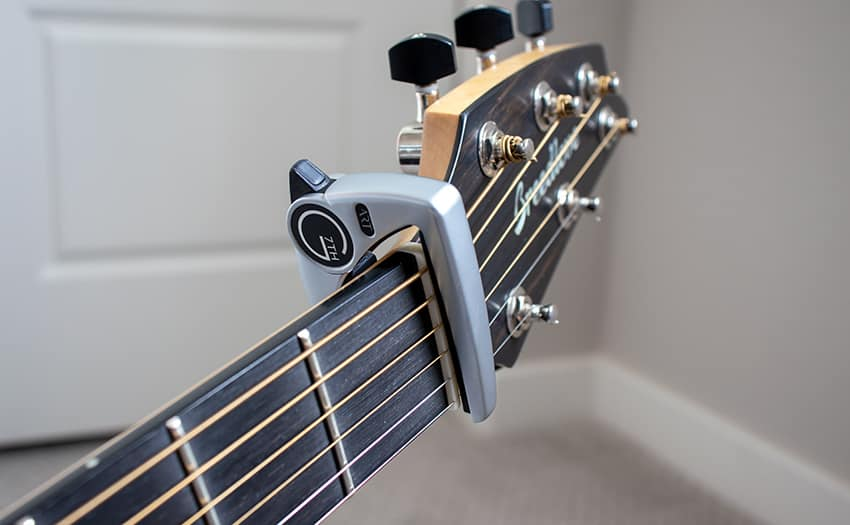 Storing the capo by gently clamping it onto the guitar's nut