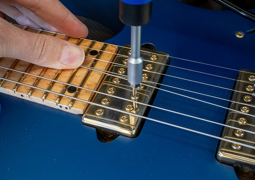Using one of the hex bits to adjust individual pickup pole pieces